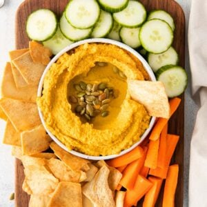 bowl of hummus with pumpkin seeds and olive oil on a dark wood cutting board with pita chips, cucumbers and carrots
