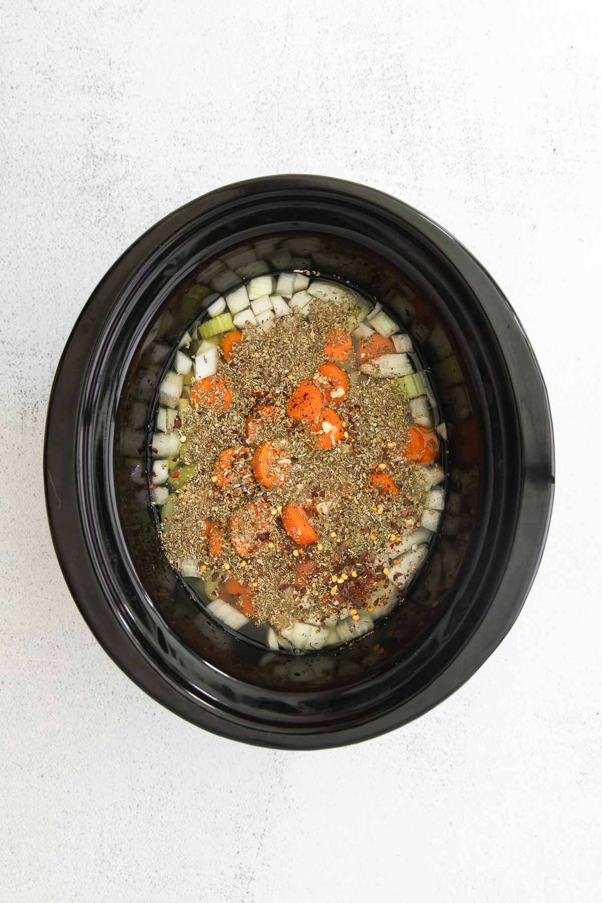 black slow cooker with diced onion, carrots and celery in chicken broth with dry spices on top