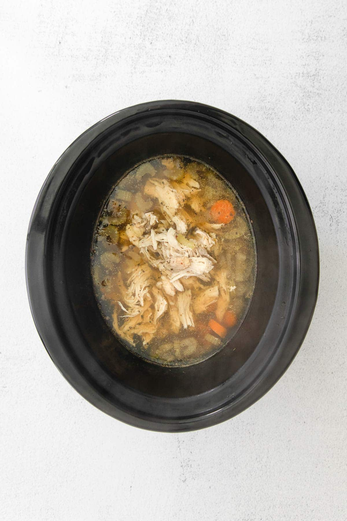black slow cooker with shredded chicken and sliced carrots in broth.