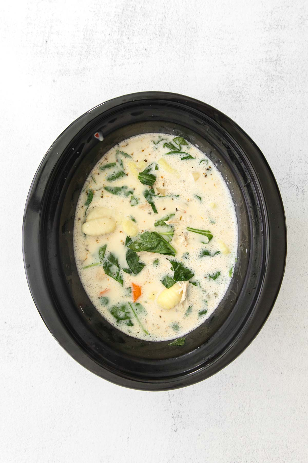 creamy soup with spinach, chicken and gnocchi in a black slow cooker