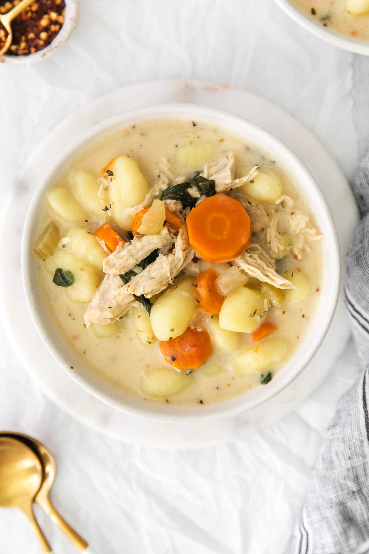 closeup of bowl of creamy chicken and gnocchi soup with carrots and spinach