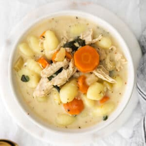 closeup of a white bowl filled with creamy chicken gnocchi soup with carrots and spinach