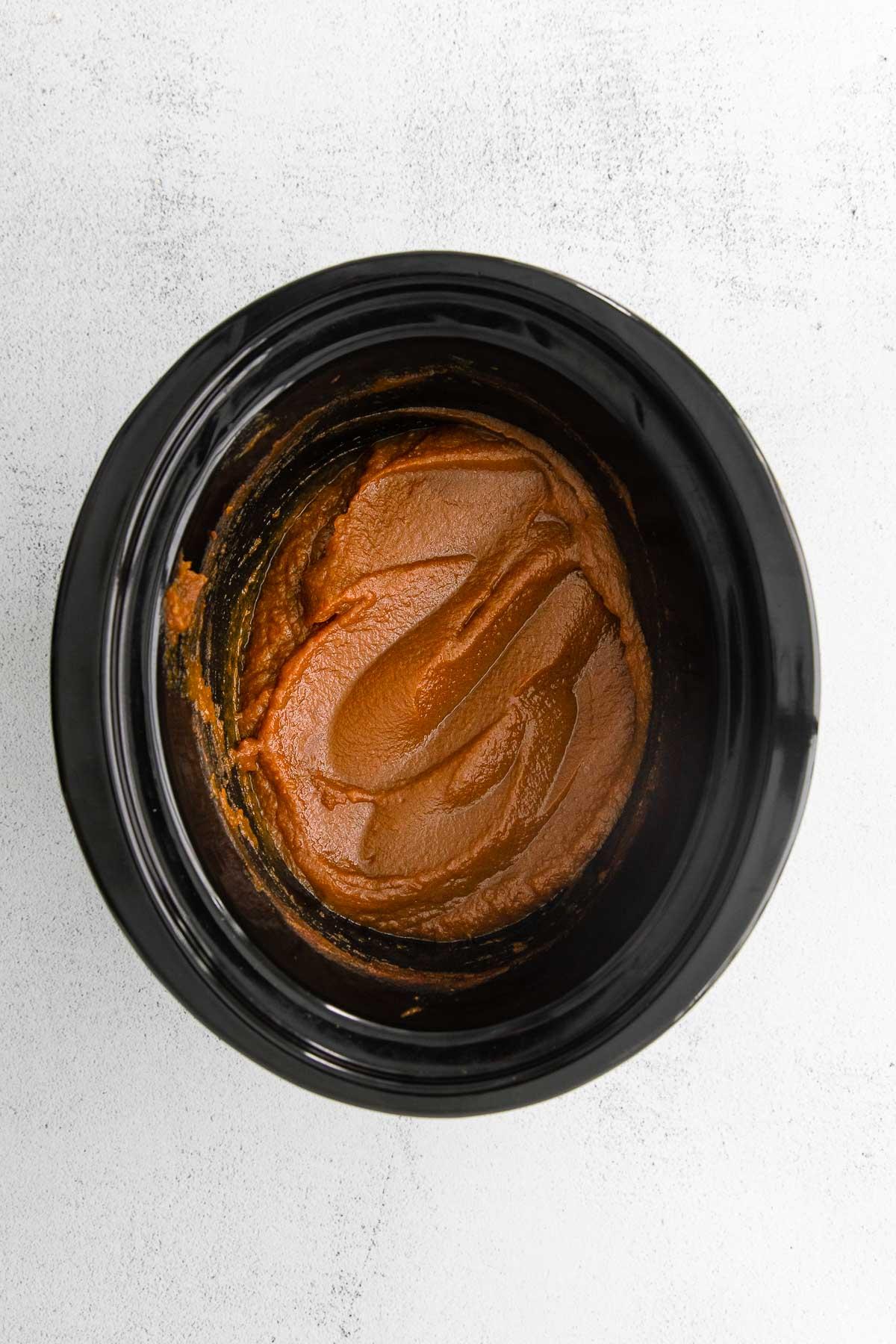 black slow cooker with homemade pumpkin butter inside