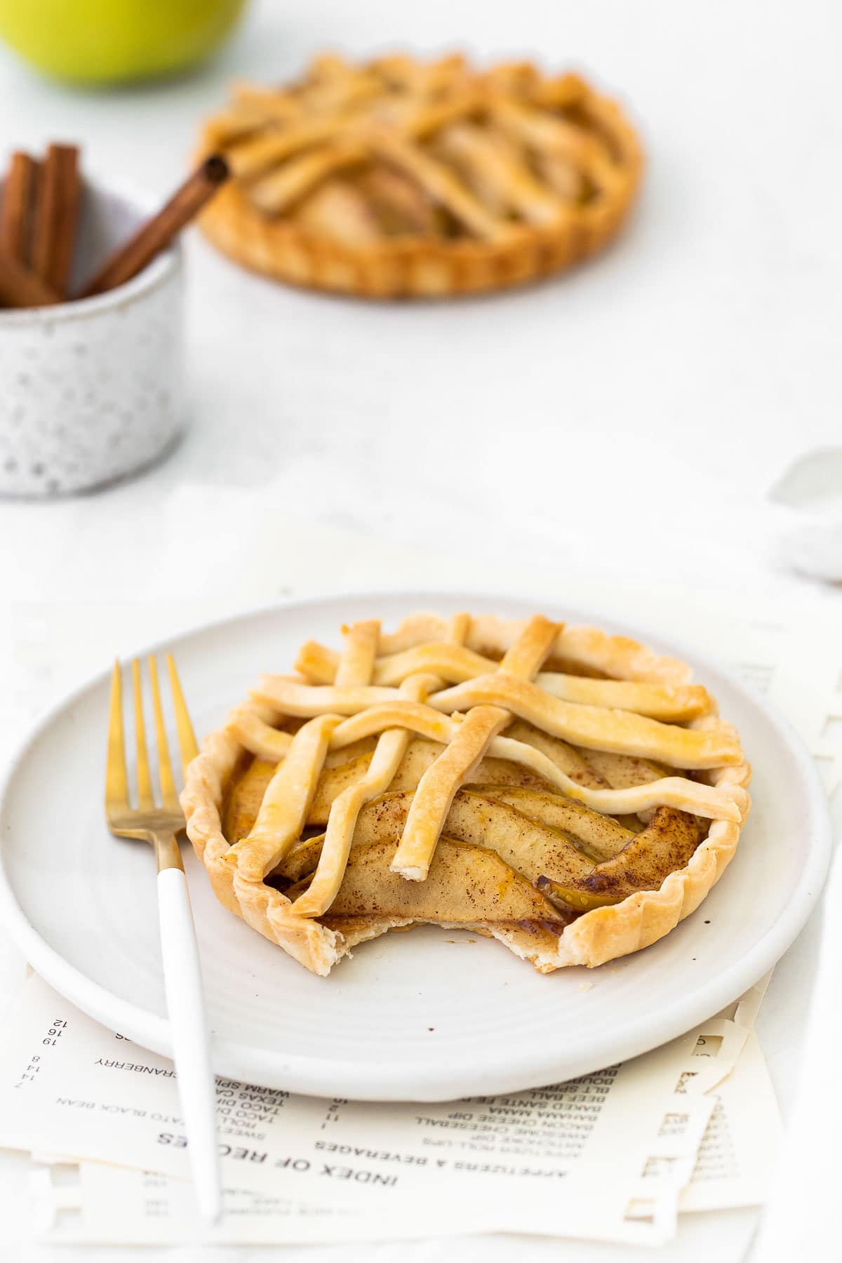 apple tart and a white and gold fork on a white round plate with a bite taken out.