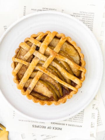 closeup of an apple tart with lattice topping on a white plate