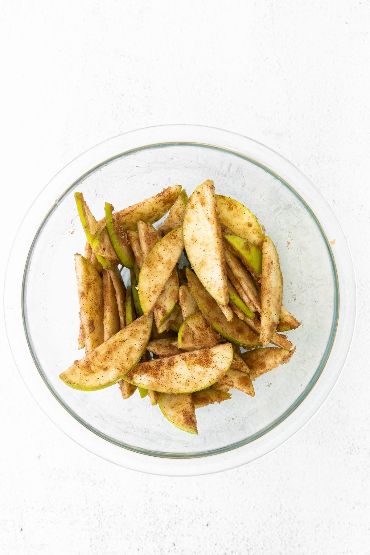 glass bowl with thinly sliced green apples tossed in cinnamon sugar