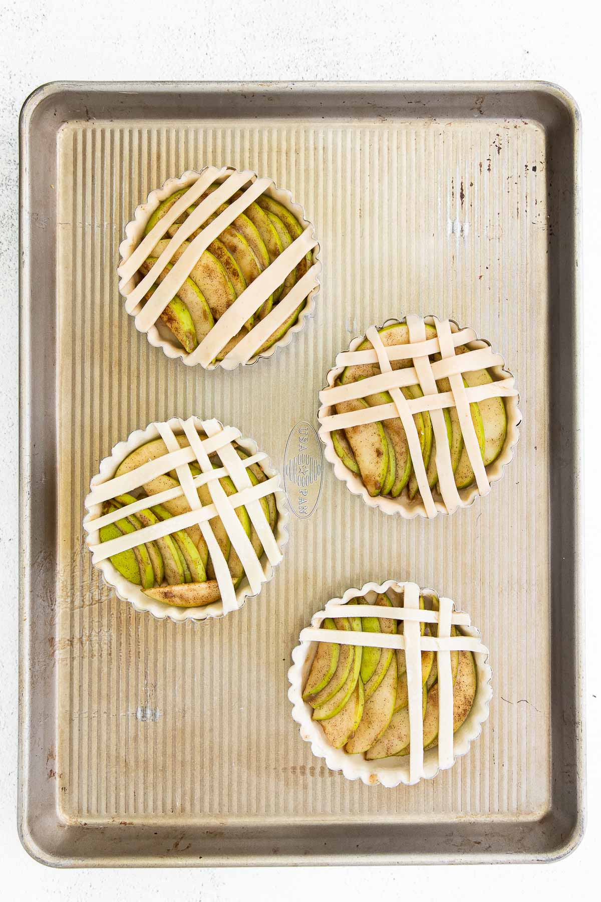 baking sheet with four tart pans filled with apple slices and topped with dough strips
