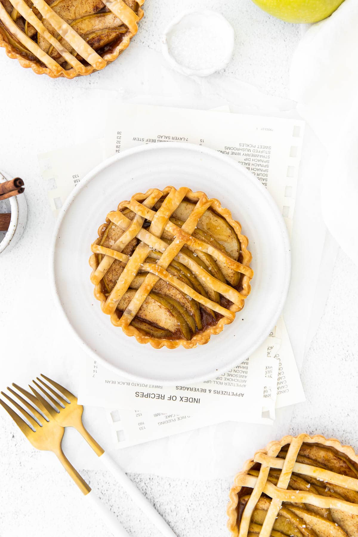 apple tart with lattice top on a white plate with two white and gold forks