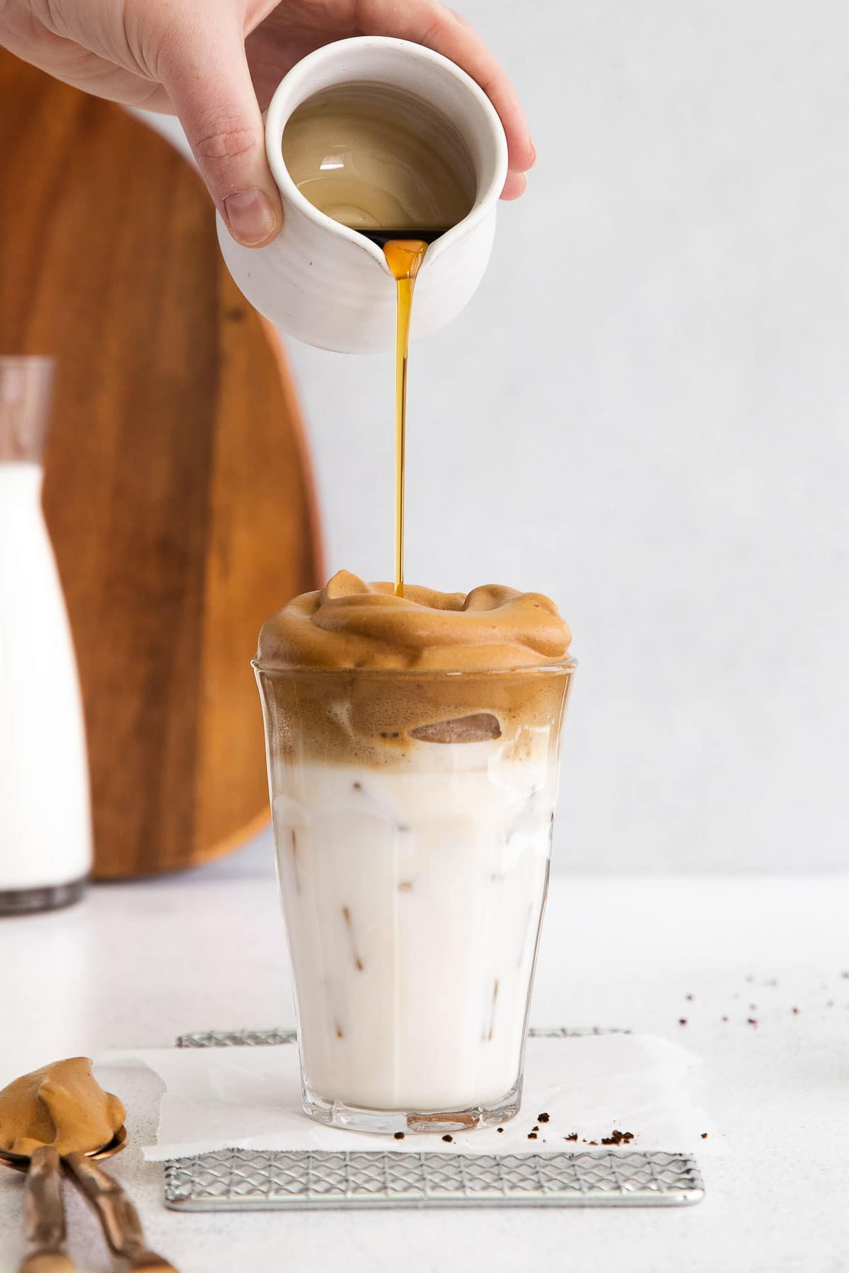 maple syrup being poured over a glass of whipped coffee