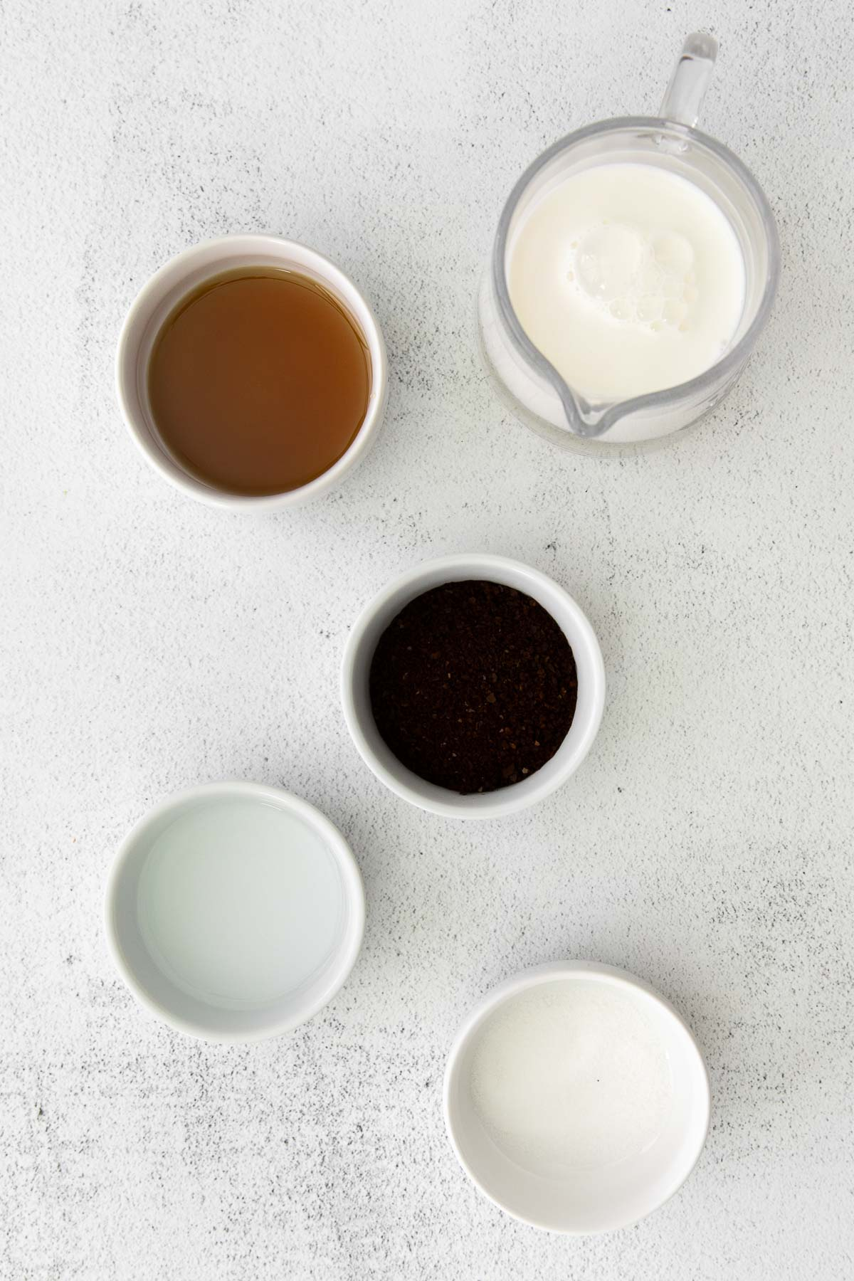 several white bowls with milk, instant coffee, milk, maple syrup for whipped coffee