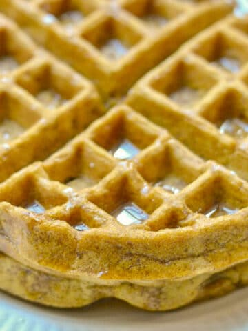 closeup of two waffles with syrup on top on a white plate
